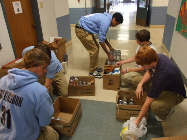 Several members of the packing crew, including (left to right) Justin Guttersohn, Patric Ripperda (hidden), Jalen Albers, Andrew Niemann, and Jon-Erik Kampwerth fill boxes with canned goods collected in the Holiday Food Drive. A total of 1,436 canned food items were collected for this year's drive.