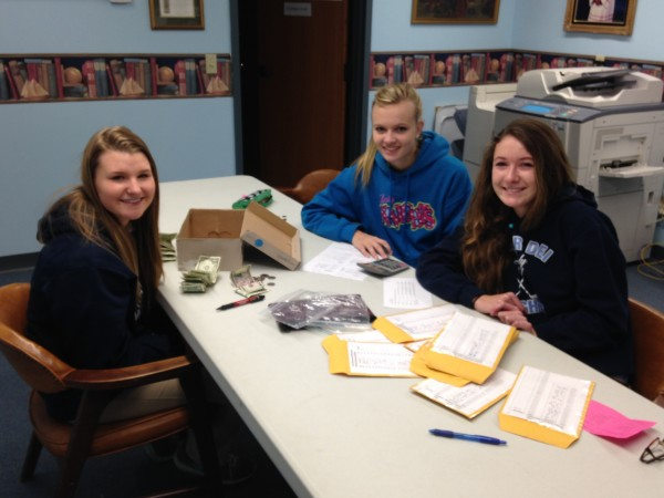 Mater Dei Catholic students count the weekly mission collections.