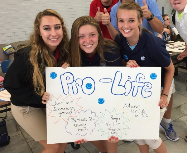 Emily Morris, Karlee Rongey, and Sophie Kuhl display the Pro- Life sign encouraging students to sign up.